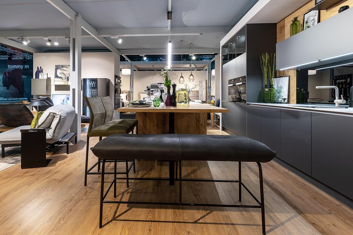 Ausstellungsraum dunkle moderne Küche und Lederhocker im Vordergrund