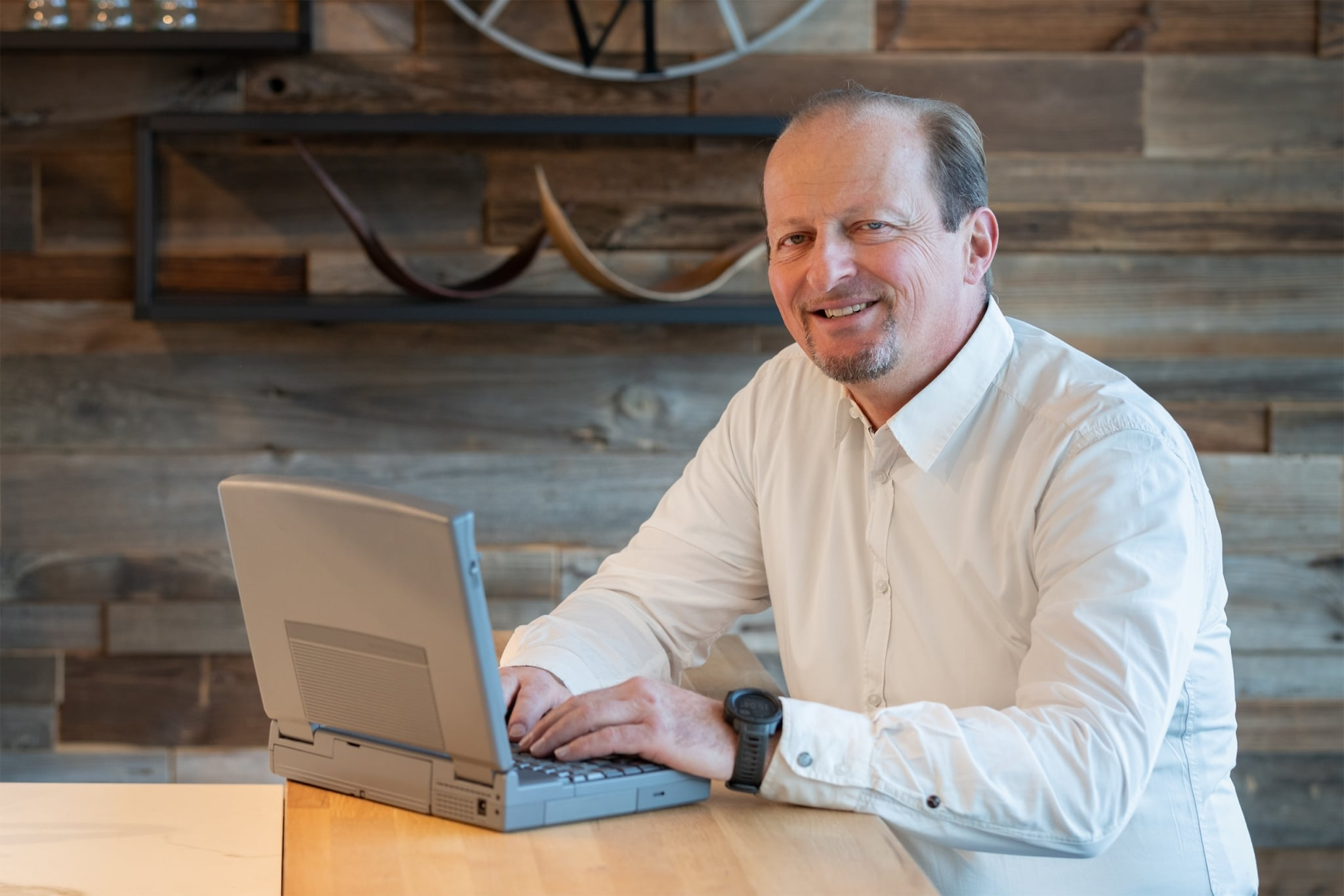 Mann mit weißem Hemd und Laptop