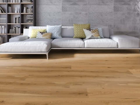 Weiße Stoffcouch mit farbigen Kissen vor grauer Wohnzimmerwand