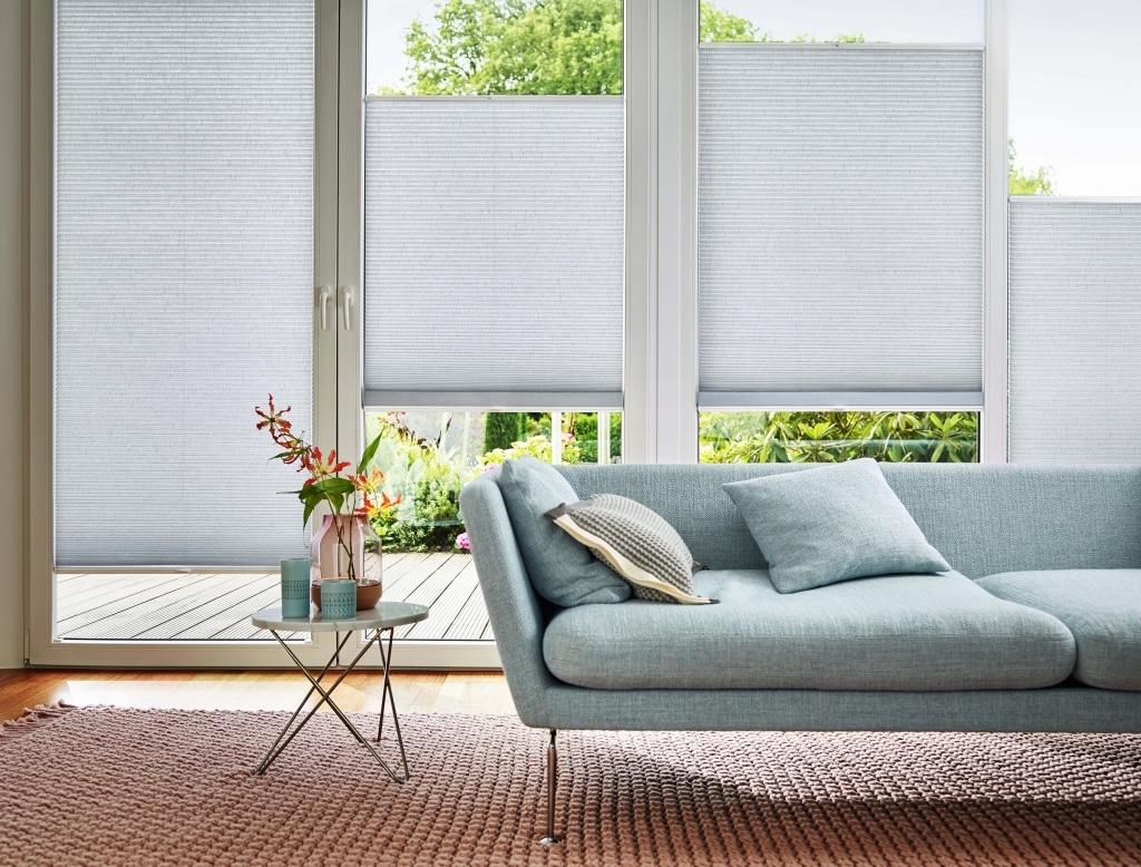 Mintfarbene Couch vor Fenster mit Sonnenschutz