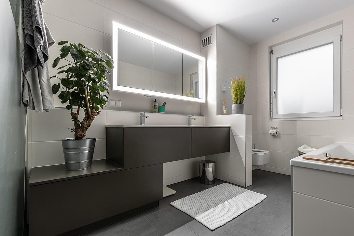 Badezimmer mit breitem, beleuchteten Spiegelschrank