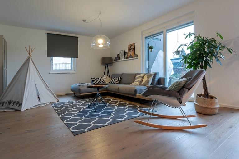 Wohnzimmer mit Couch, Schaukelstuhl, Tipi und Sonnenschutz an den Fenstern