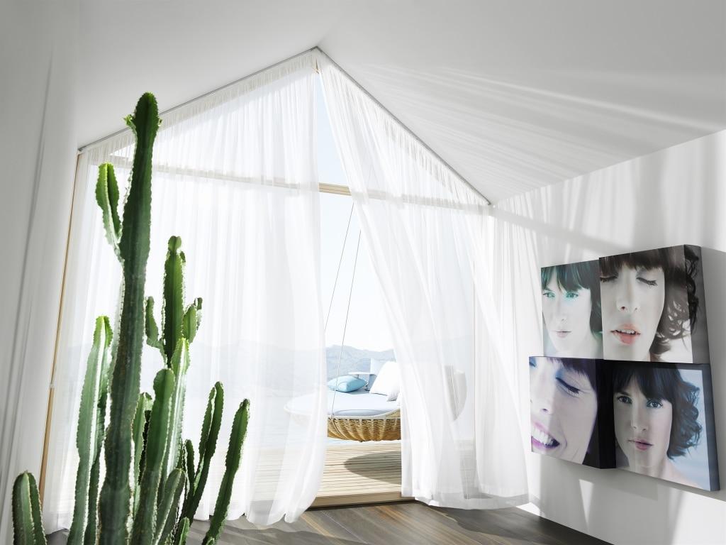 Weißes Zimmer am Wasser mit Kaktus und Stoffvorhang als Sonnenschutz