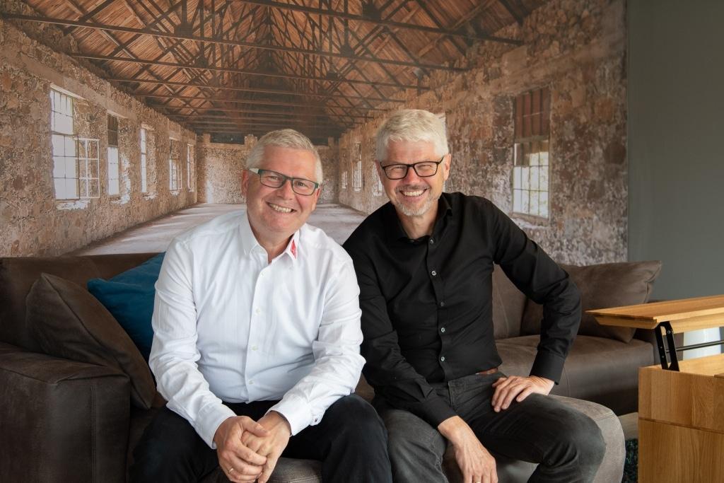 zwei Männer lachen und sitzen auf einer braunen Ledercouch