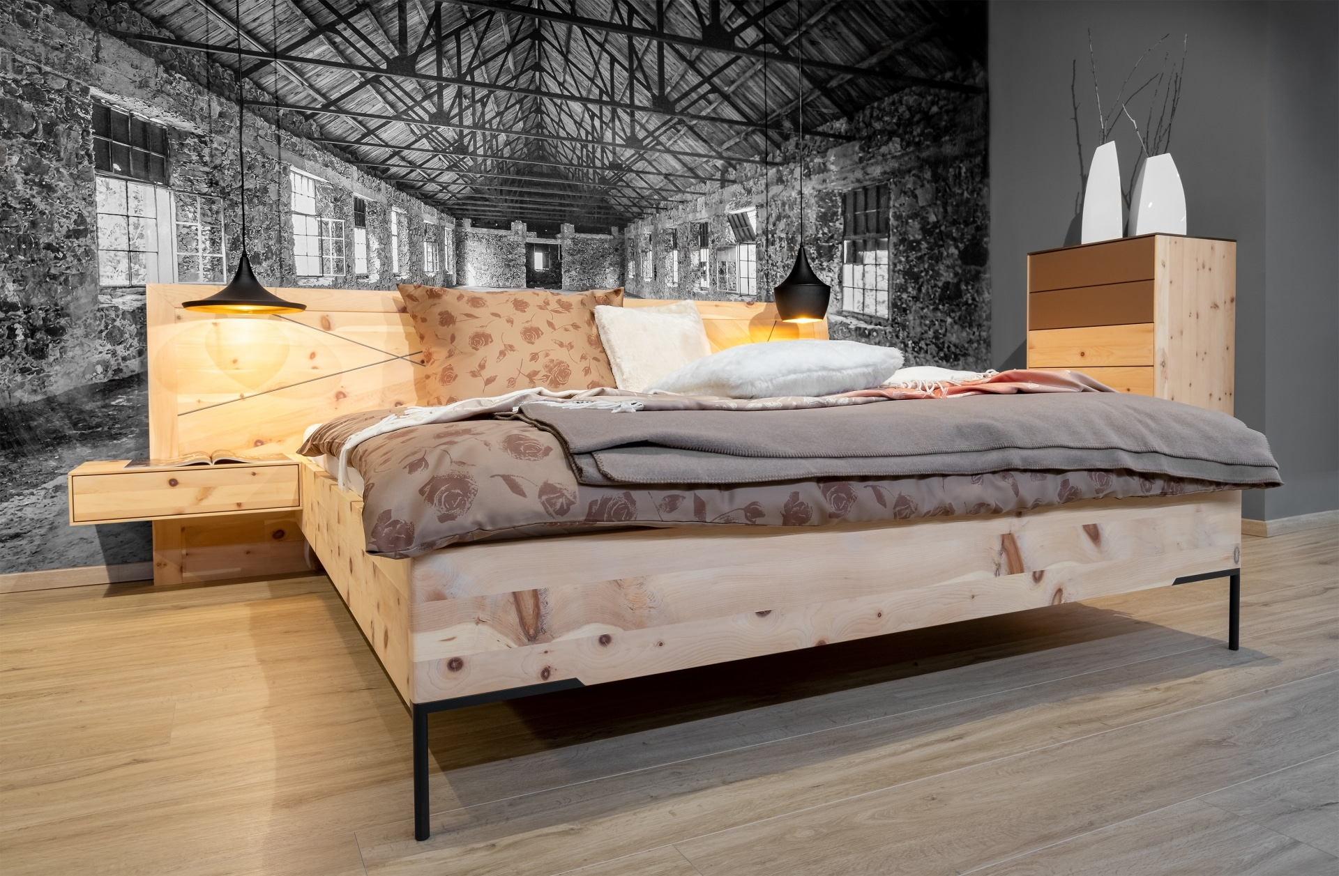 Bett mit Wandleuchten vor Akzenttapete