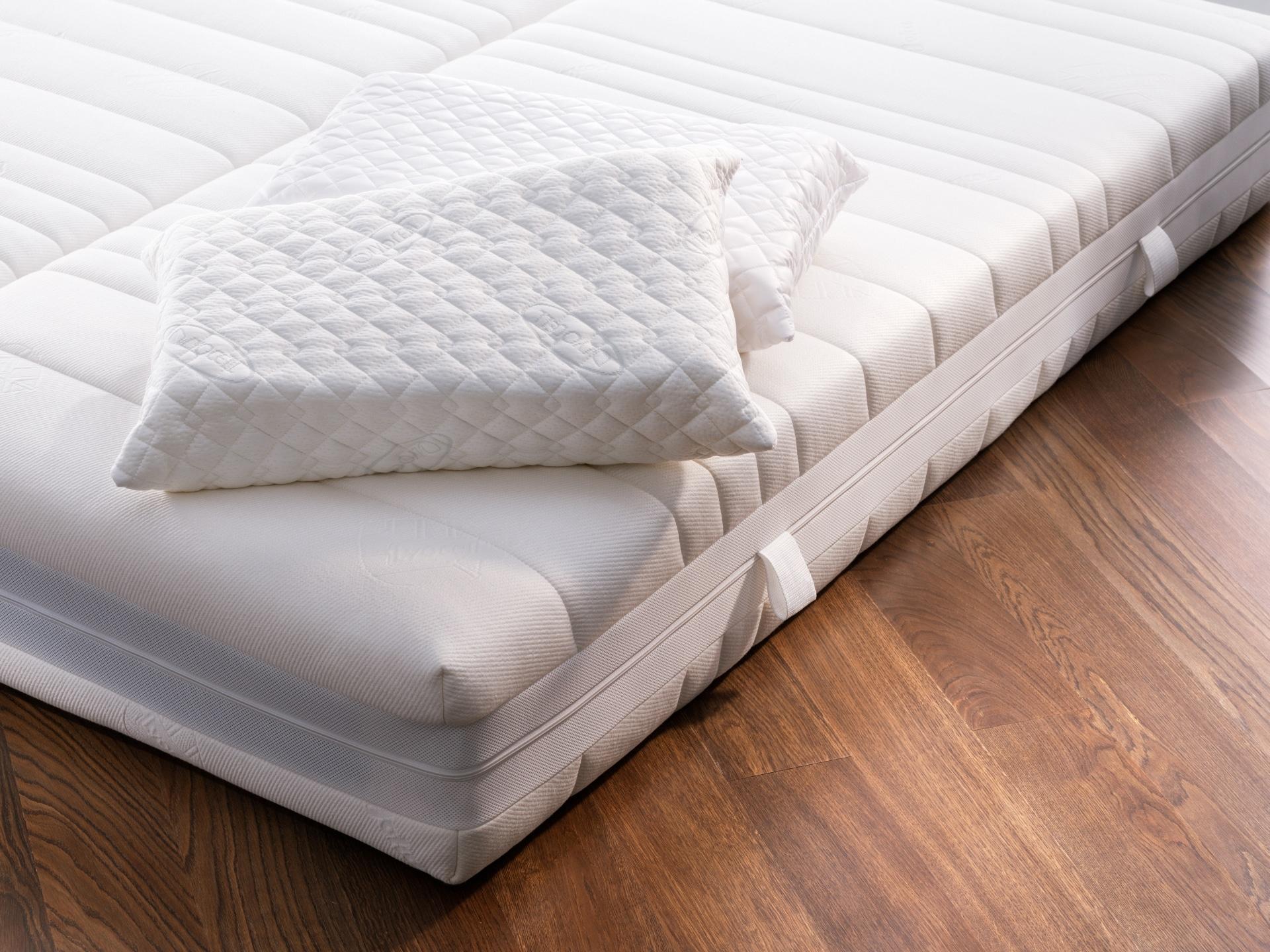 Matratze und Kissen auf Holzboden
