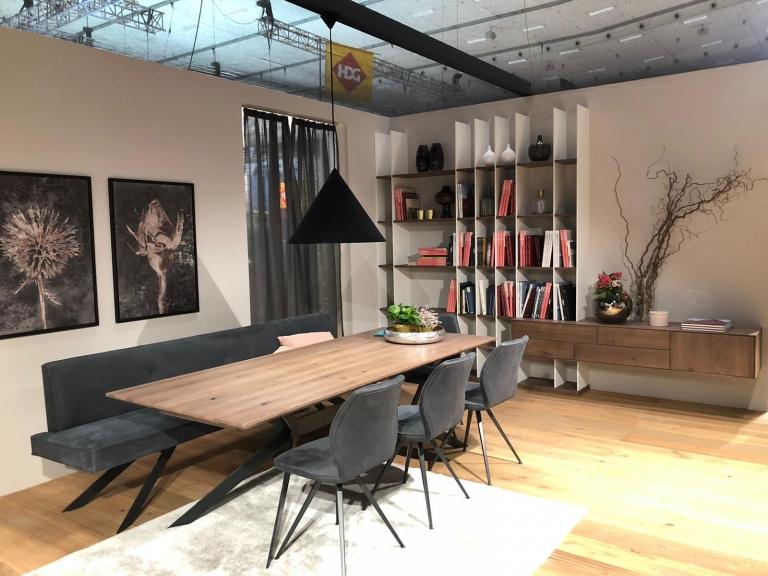 Esszimmer in Ausstellungshaus Holztisch und graue Stoffsessel und -bank