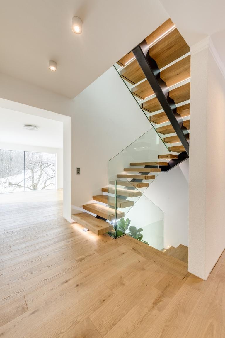 heller, offener Stiegenaufgang mit brauner Stiege und weißem Raum