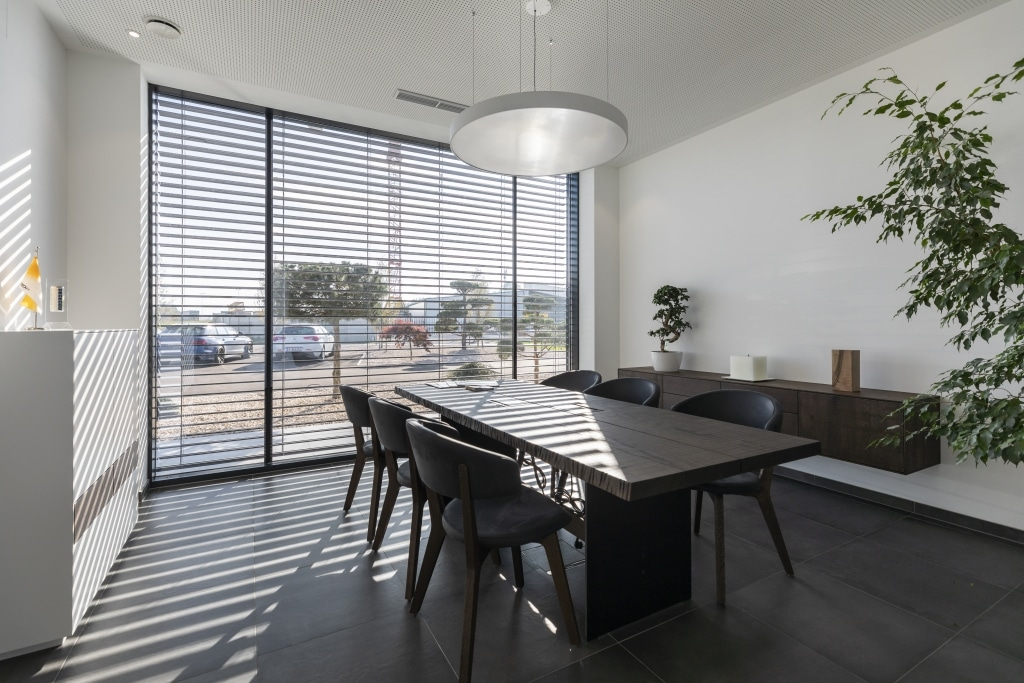 Massiver Holzesstisch in lichtdurchflutetem Raum