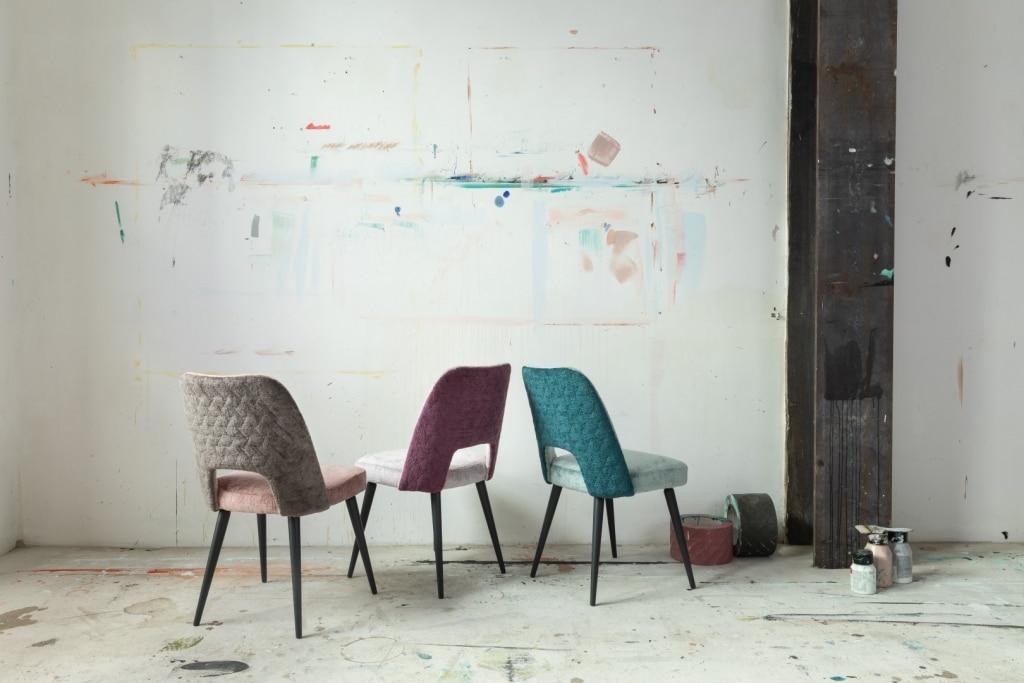 drei bunte Stühle vor weißen Wand