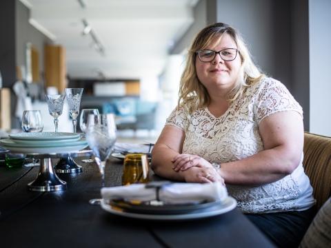 Frau mit Brille sitzt an gedecktem Esstisch