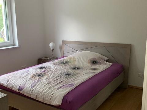 Doppelbett mit weißem und violetten Überzug