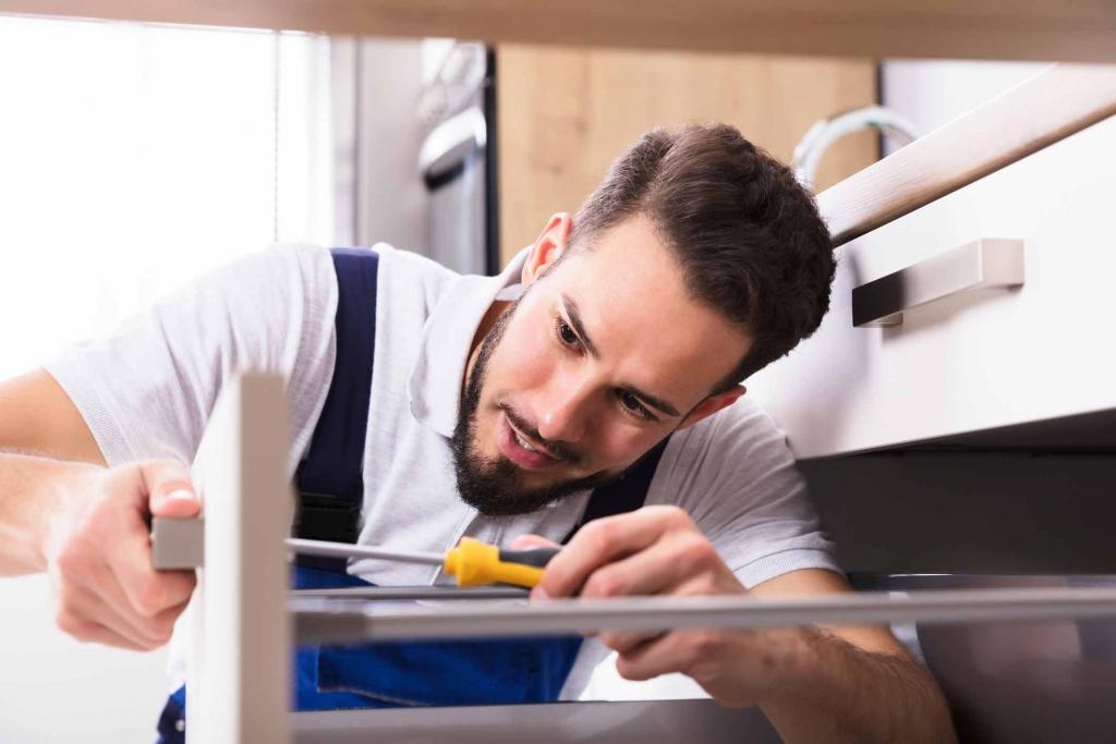 Mann mit Schraubenzieher beim Aufbau einer Küche